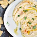 This thick and creamy Classic Homemade Hummus spread out across a large off-white plate topped with pine nuts, paprika and olive oil surrounded by pita chips
