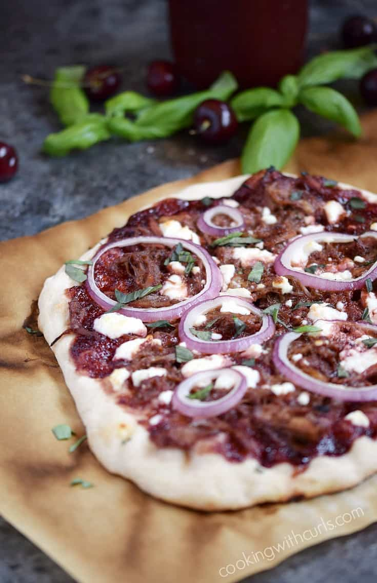 Cherry Bourbon Barbecue Pork Pizza will become a family favorite! Sweet and tangy sauce, salty shredded pork, and tangy Chevre make a winning combination cookingwithcurls.com