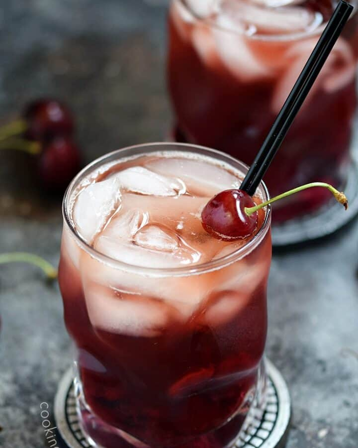 Two Cherry Whiskey Smash cocktails in clear glasses with a fresh cherry garnish and thin black straw.