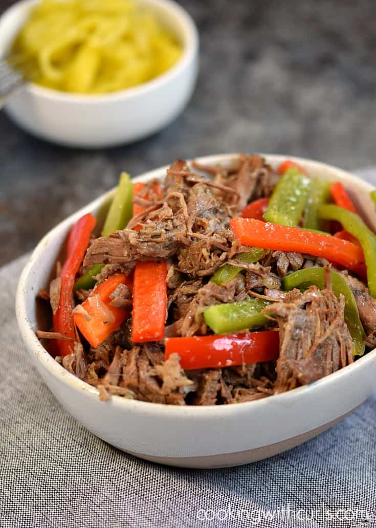 Instant Pot Italian Beef shredded beef with sautéed green and red bell pepper slices in a white bowl.