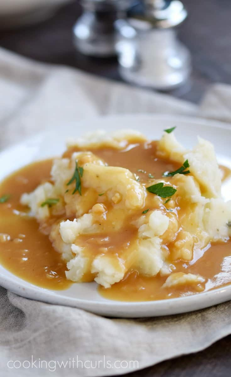 Creamy and fluffy Instant Pot Mashed Potatoes topped with savory beef gravy | cookingwithcurls.com