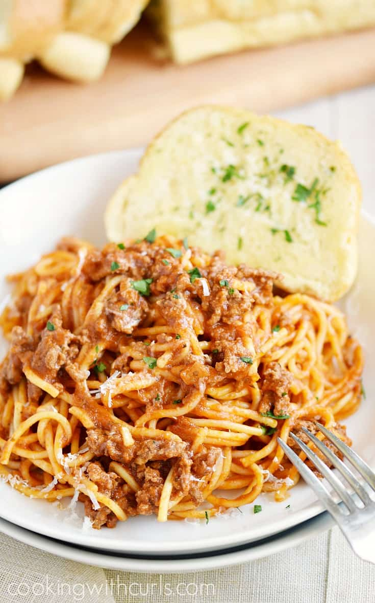 Spaghetti with meat sauce on a white plate with garlic bread on the side.
