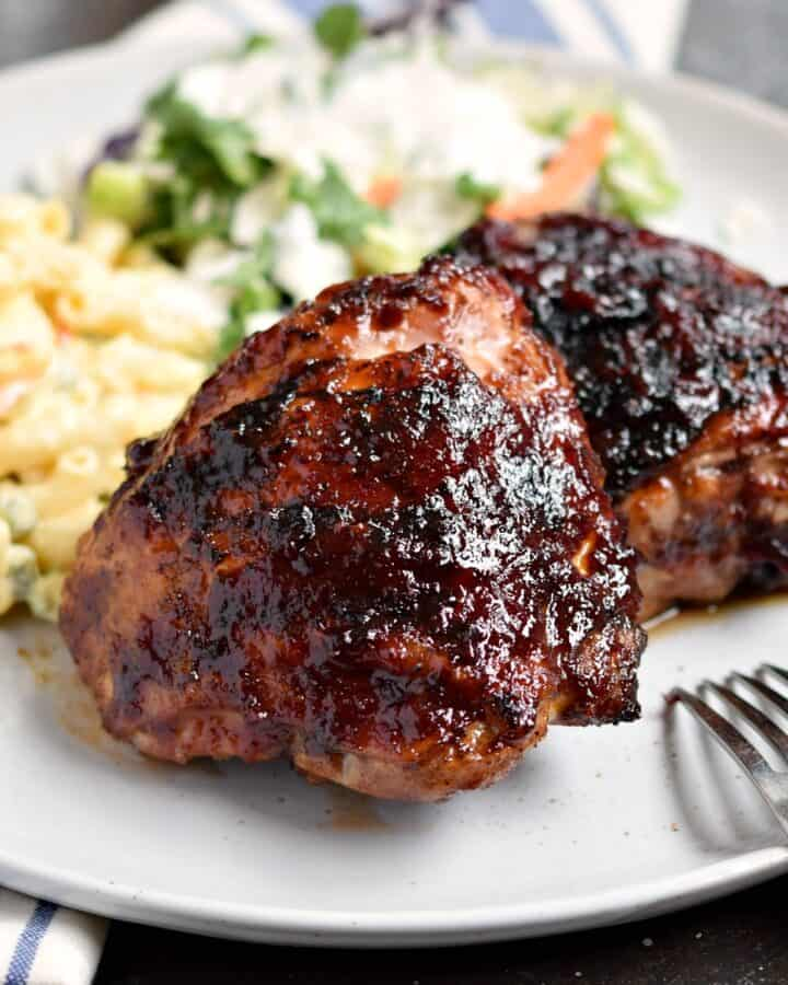 grilled barbecue chicken thighs, bone-in on a white plate with potato salad and a green salad.