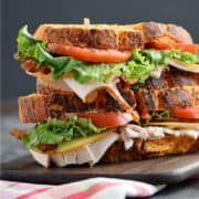 Two sandwiches with turkey, bacon, lettuce, cheese, and tomato slices on tomato bread stacked on top of each other.