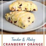 Two cranberry-orange scones on a white plate with title graphic across the bottom.