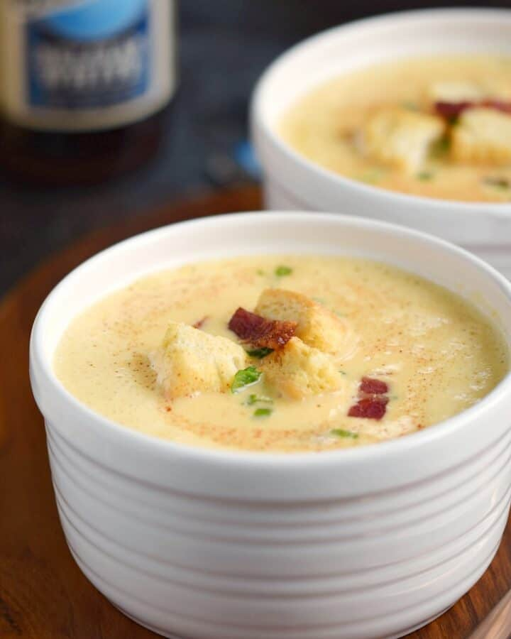 Two bowls of rich and creamy Instant Pot Cheddar-Ale Soup in white bowls garnished with croutons and bacon bits.