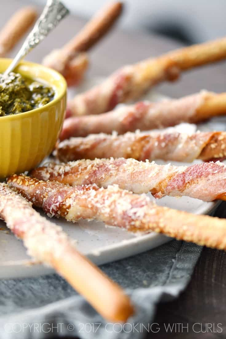 Bacon-Wrapped Breadsticks Appetizer sprinkled with spicy Parmesan and served with Basil Pesto is a perfectly simple appetizer for your next party! COPYRIGHT © 2017 COOKING WITH CURLS