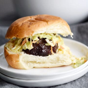 Meatball topped with coleslaw and a cocktail bun.