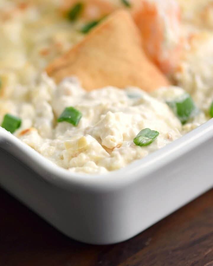 Seafood Artichoke Dip in a white baking dish with a chip sticking out of the top.