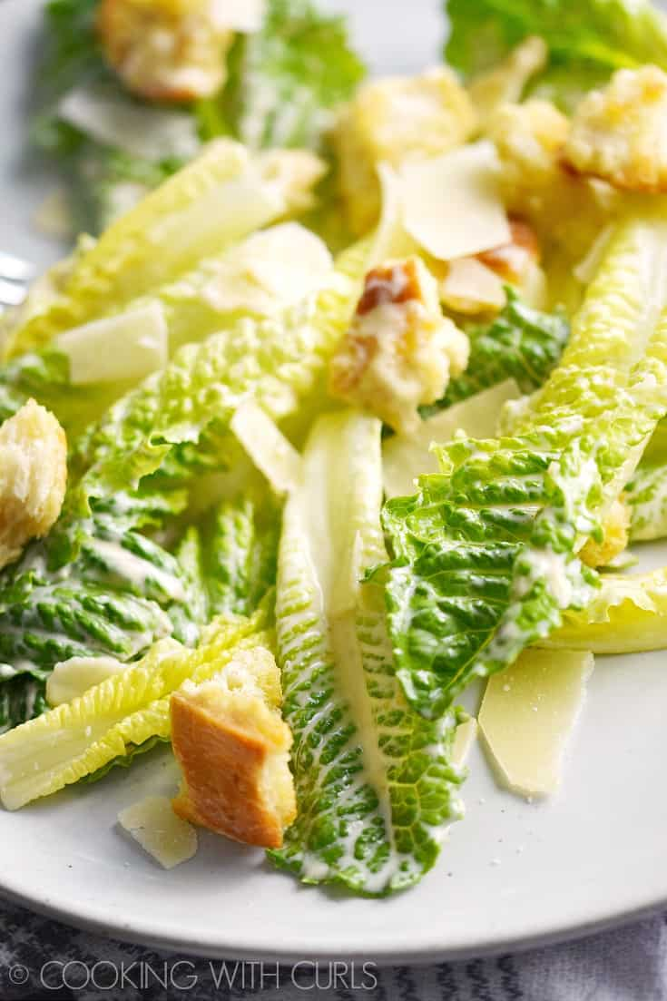Classic Caesar Salad with romaine hearts, Caesar salad dressing, shaved Parmesan and homemade garlic croutons is the perfect start to any meal! © COOKING WITH CURLS