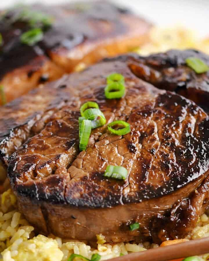 A steak and a piece of salmon on a bed of fried rice.