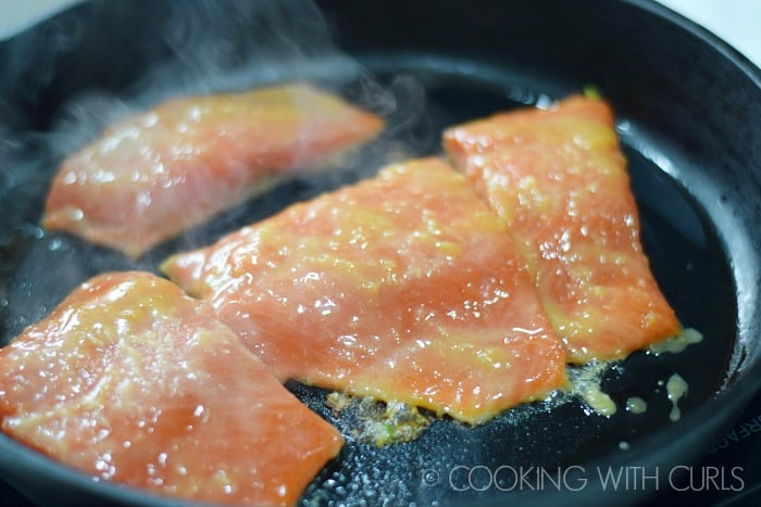 Four Salmon fillets sizzling in a cast iron skillet © COOKING WITH CURLS