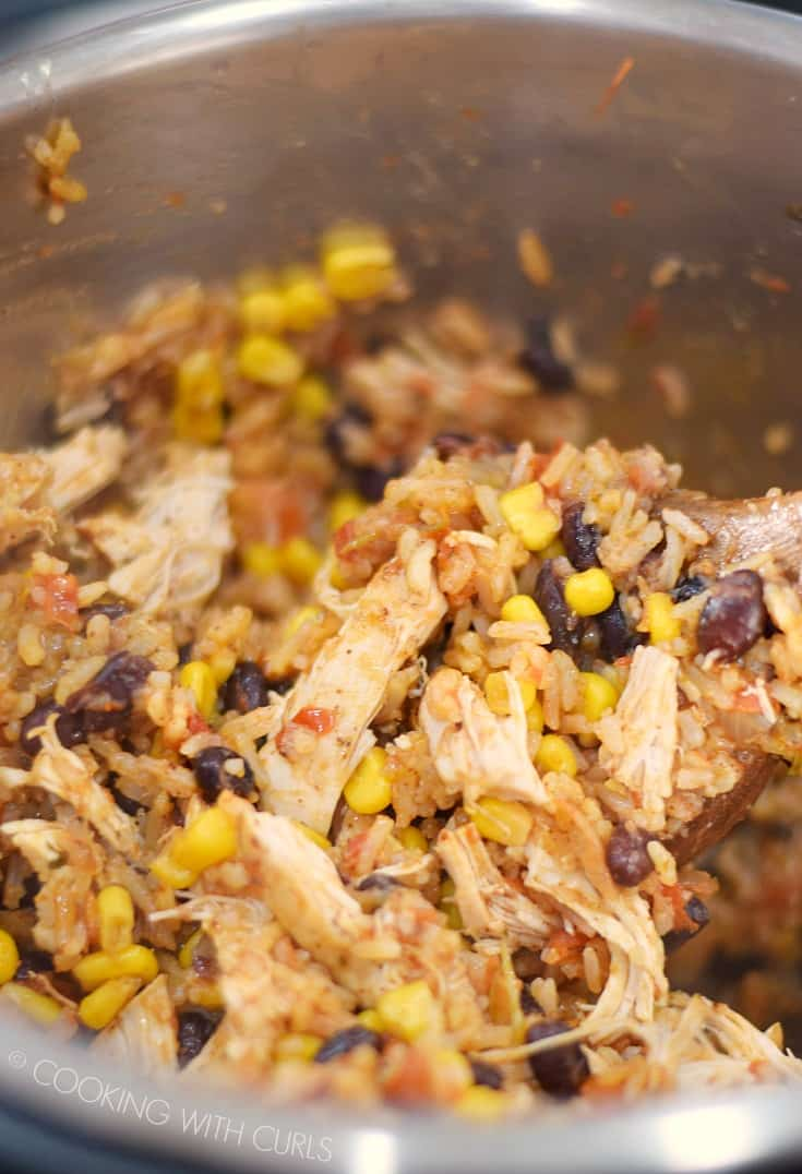 Stirring the Instant Pot Chicken Taco Bowls together with a large wooden spoon