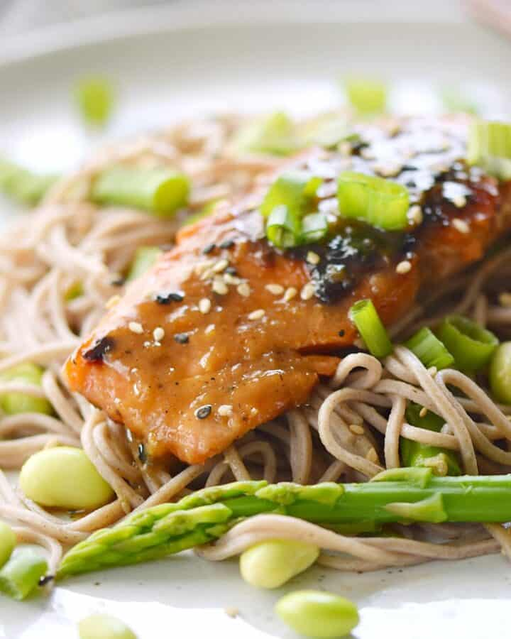 Miso-Ginger Glazed Salmon laying on a bed of soba noodles, asparagus and beans.