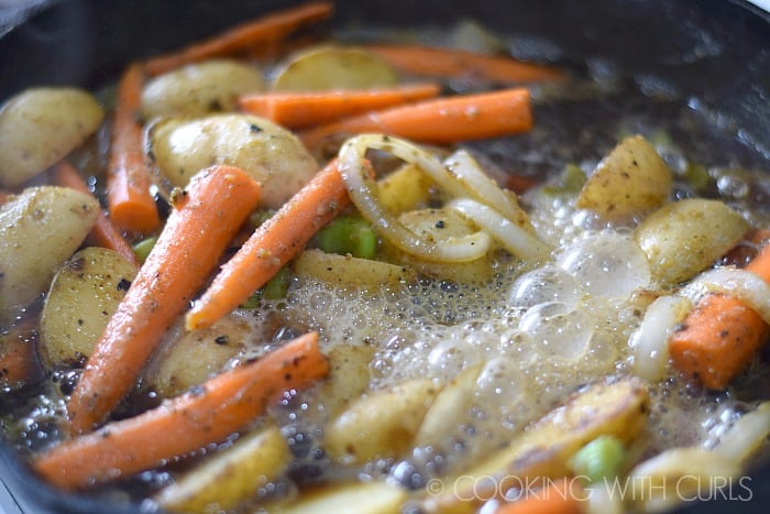 Add the beer to the vegetables in the cast iron skillet © COOKING WITH CURLS