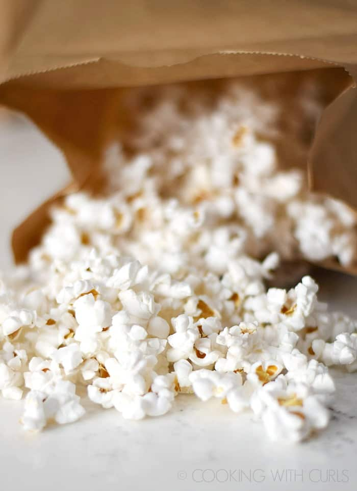 Fresh popped popcorn spilling out of a brown paper bag © COOKING WITH CURLS