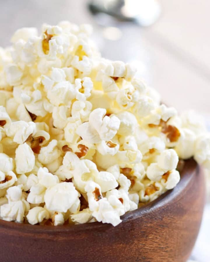 fluffy white popcorn in a wood bowl overflowing below.