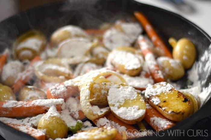 Sprinkle flour over the vegetables in the cast iron skillet © COOKING WITH CURLS