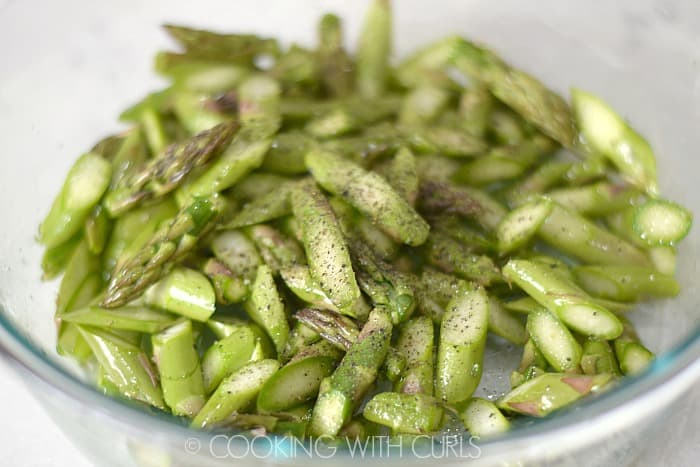Bite size pieces of asparagus tossed in a bowl with oil, salt and pepper © COOKING WITH CURLS