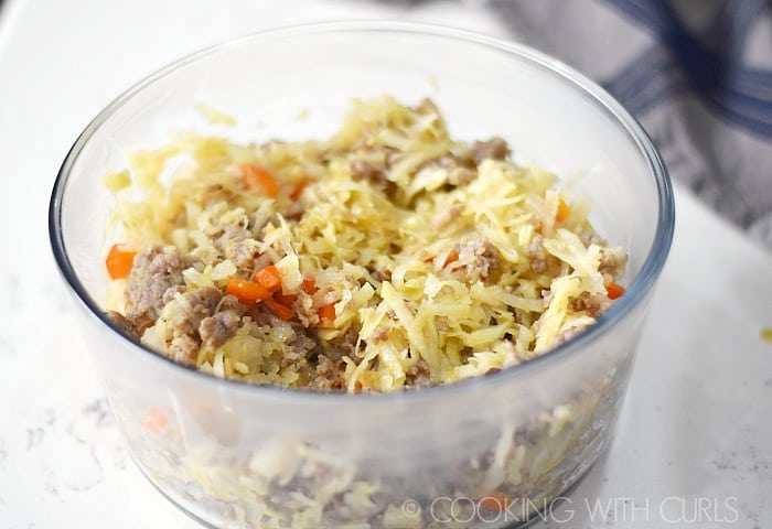 Glass baking dish with the browned sausage, onion, pepper, and hash browns © COOKING WITH CURLS