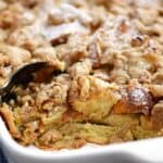 a black spoon scooping cinnamon french toast bake out of the white baking dish.