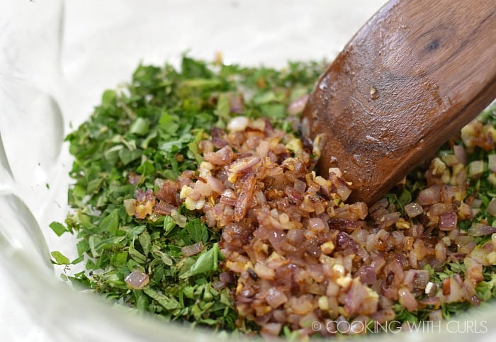 Add the sauted onions and garlic to the fresh chopped herbs in a large bowl © COOKING WITH CURLS