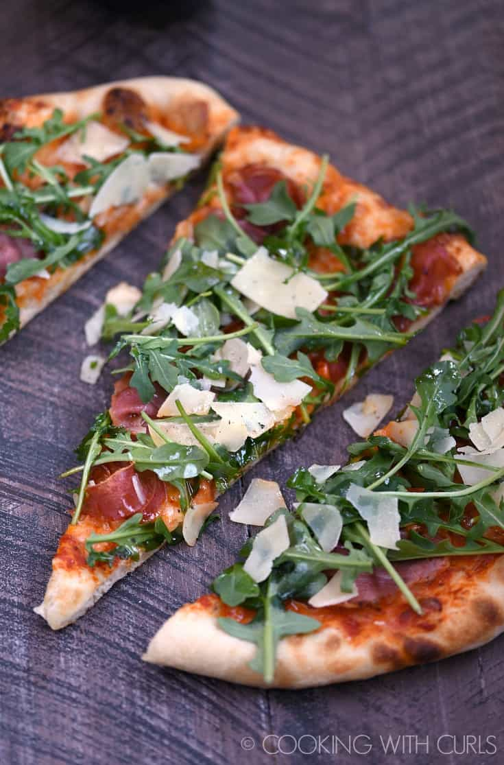 Chewy crust, tangy tomato sauce, salty prosciutto, and peppery arugula blend to create the ultimate Prosciutto-Arugula Pizza at home in your oven or grill. © COOKING WITH CURLS
