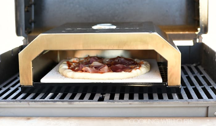 Slide prepared pizza onto a heated baking stone © COOKING WITH CURLS