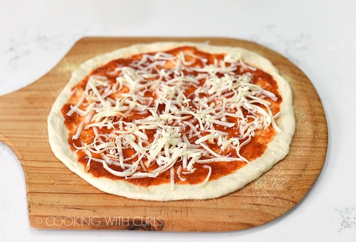Sprinkle grated mozzarella cheese over the pizza sauce © COOKING WITH CURLS