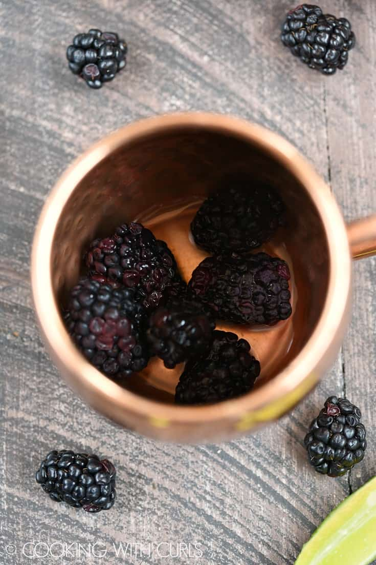Add the blackberries and lime juice to a copper mug © COOKING WITH CURLS