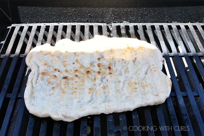 Grill the pizza dough then flip it over © COOKING WITH CURLS