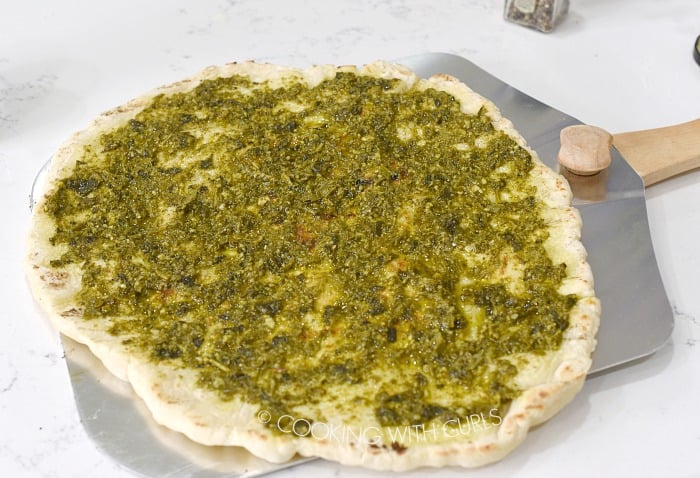 Spread pesto over the grilled pizza crust © COOKING WITH CURLS