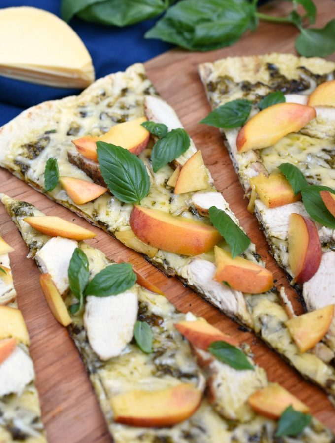 Sweet peaches, salty Gruyere, and a grilled crust combine to make an amazing Grilled Chicken and Peach Pesto Pizza that everyone will love! © COOKING WITH CURLS