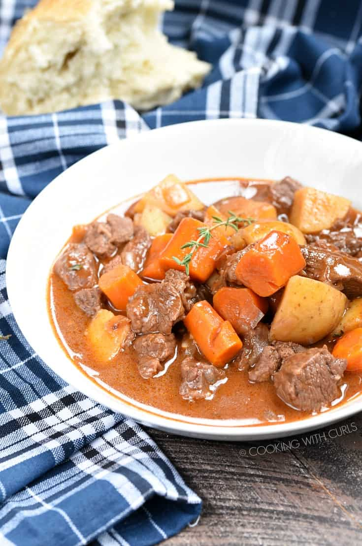 Instant Pot Beef Stew with large chunks of beef, carrots and potatoes in a white bowl.