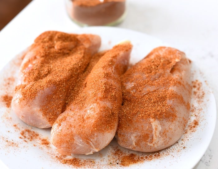 Taco seasoning sprinkled over the chicken breasts on a white plate.