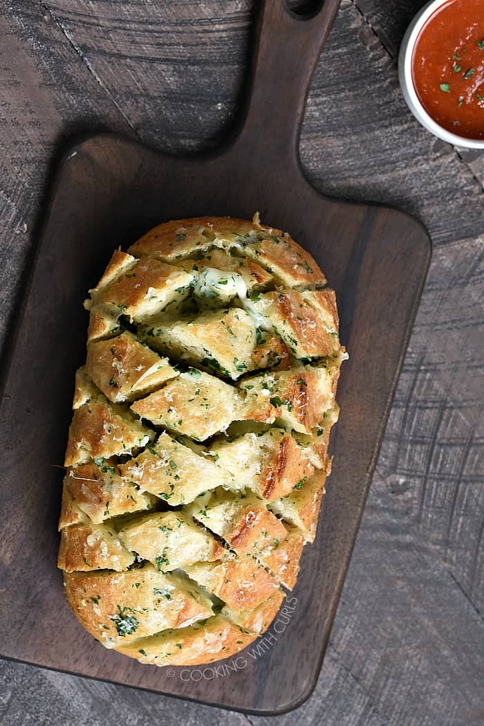 Crusty bread, garlic butter, and lots of cheese create an amazing Cheesy Garlic Pull-Apart Bread that everyone will be fighting over! cookingwithcurls.com