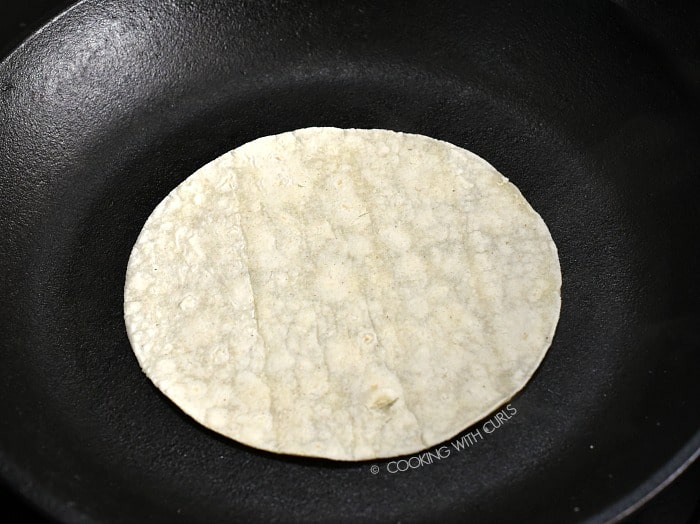 Corn tortilla heated in a cast iron skillet cookingwithcurls.com
