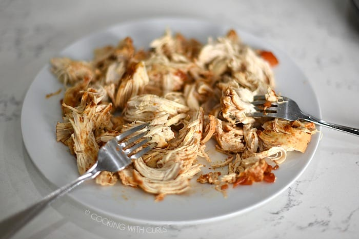 Chicken breasts shredded on a plate with two forks cookingwithcurls.com