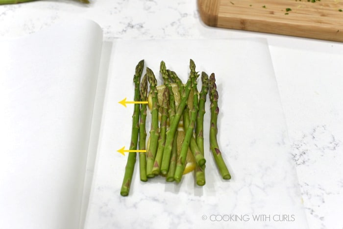 Place the asparagus spears on top of the lemon slices on the parchment paper cookingwithcurls.com