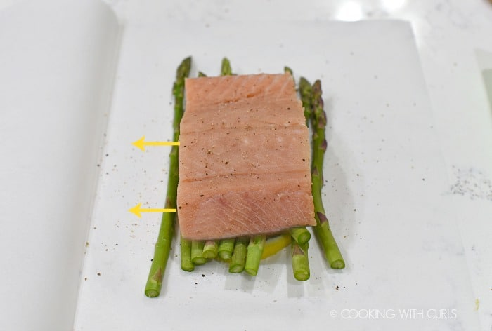 Salmon placed on top of the asparagus spears and sprinkled with salt and pepper cookingwithcurls.com