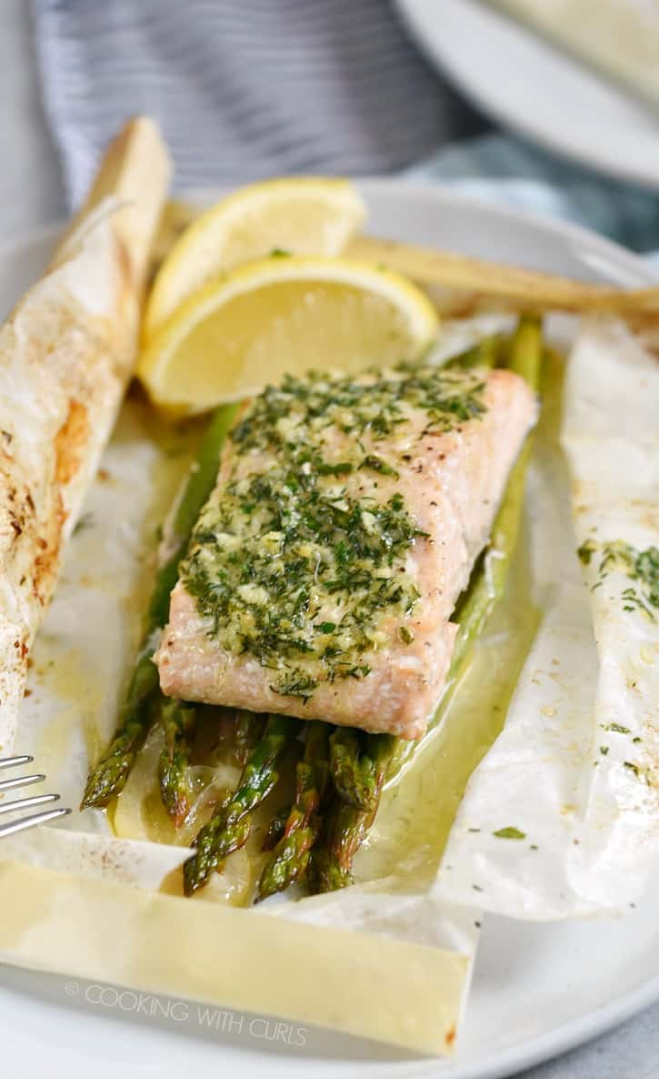 This Baked Salmon in Parchment with Asparagus Lemon and Dill is loaded with flavor from the compound butter, and stays tender and moist in it's pouch! cookingwithcurls.com