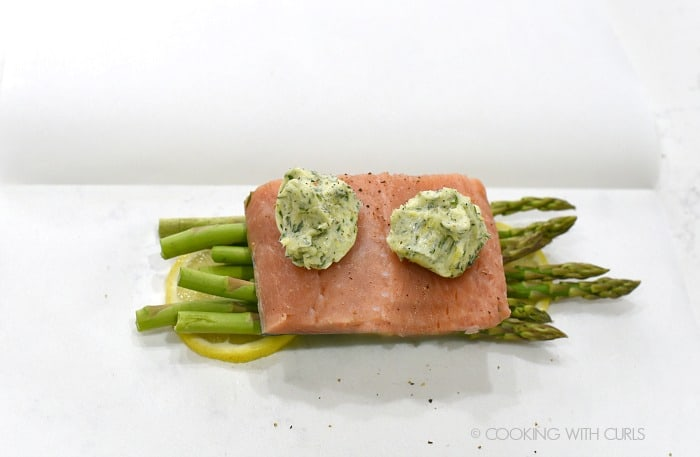 Two dollops of compound butter top the salmon on a bed of asparagus and lemon slices cookingwithcurls.com