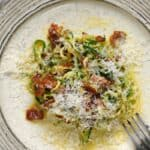 A creamy sauce, crispy bacon and grated Parmesan surround zucchini noodles to create the ultimate Zucchini Carbonara served on a beige plate