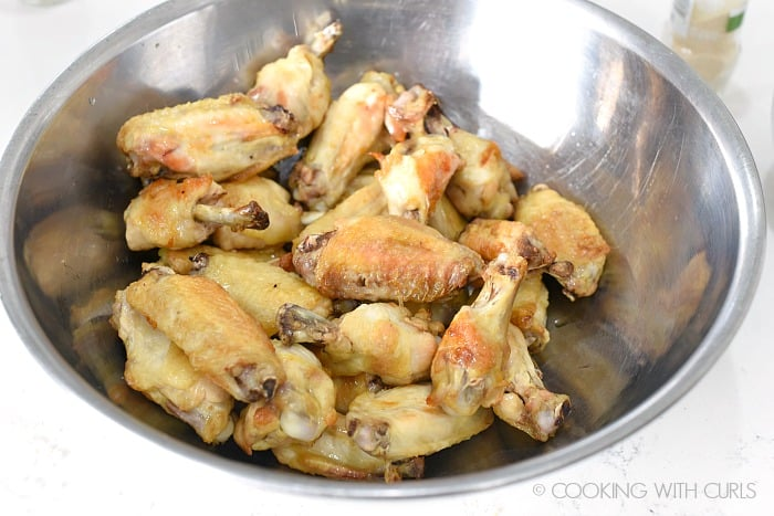 Baked chicken wings in a large stainless steel bowl cookingwithcurls.com