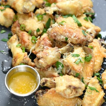 Garlic Parmesan Chicken Wings are baked crispy then tossed in a delicious garlic-Parmesan sauce that will have all of your party guests fighting for more! cookingwithcurls.com