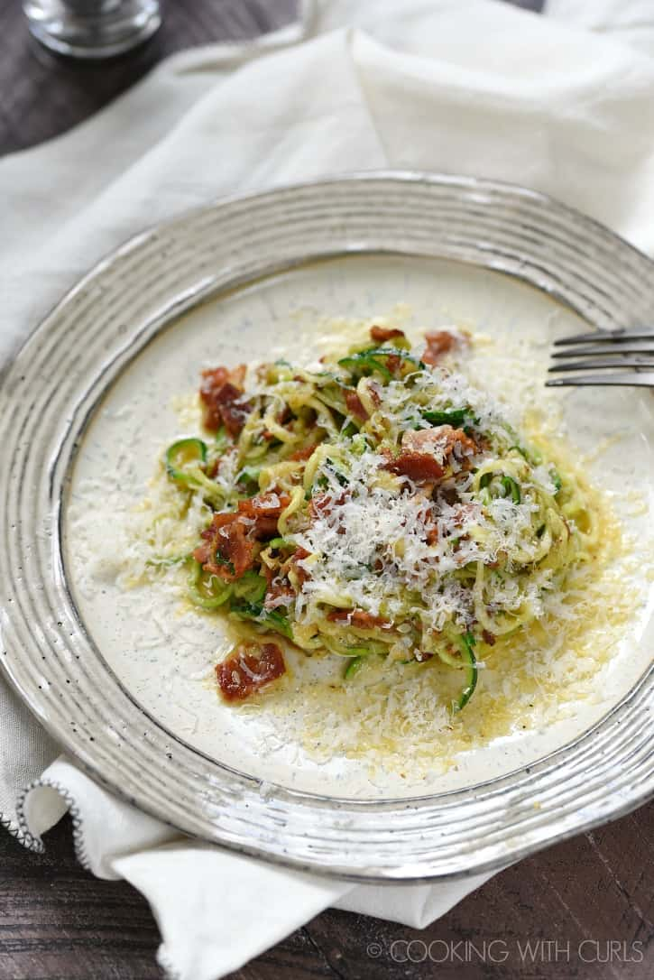 a beige plate with zucchini noodles, parmesan and bacon pieces in a creamy egg sauce