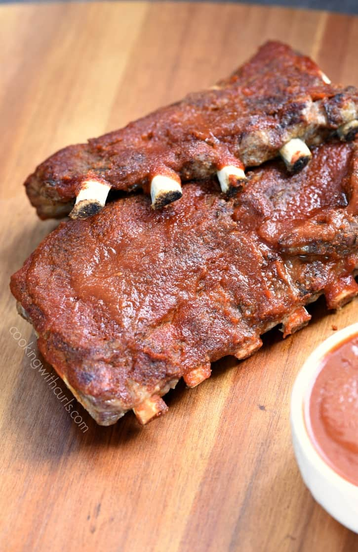 bbq ribs laying on a wooden board covered in bbq sauce with the corner of a small bowl of sauce in the bottom right hand corner