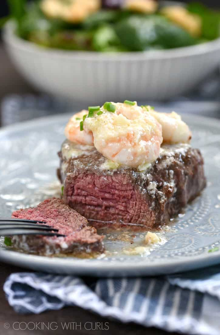 a cut filet mignon sitting on a gray plate topped with shrimp scampi