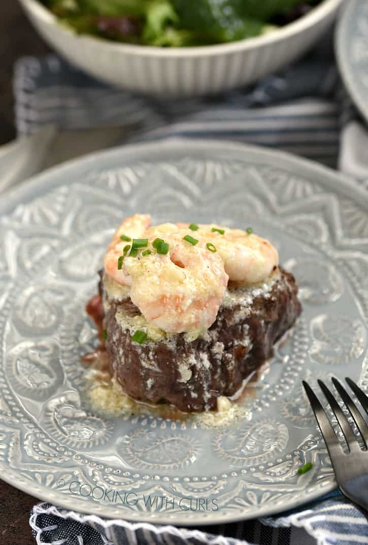 shrimp topped filet on a gray plate with a salad in a white bowl in the background