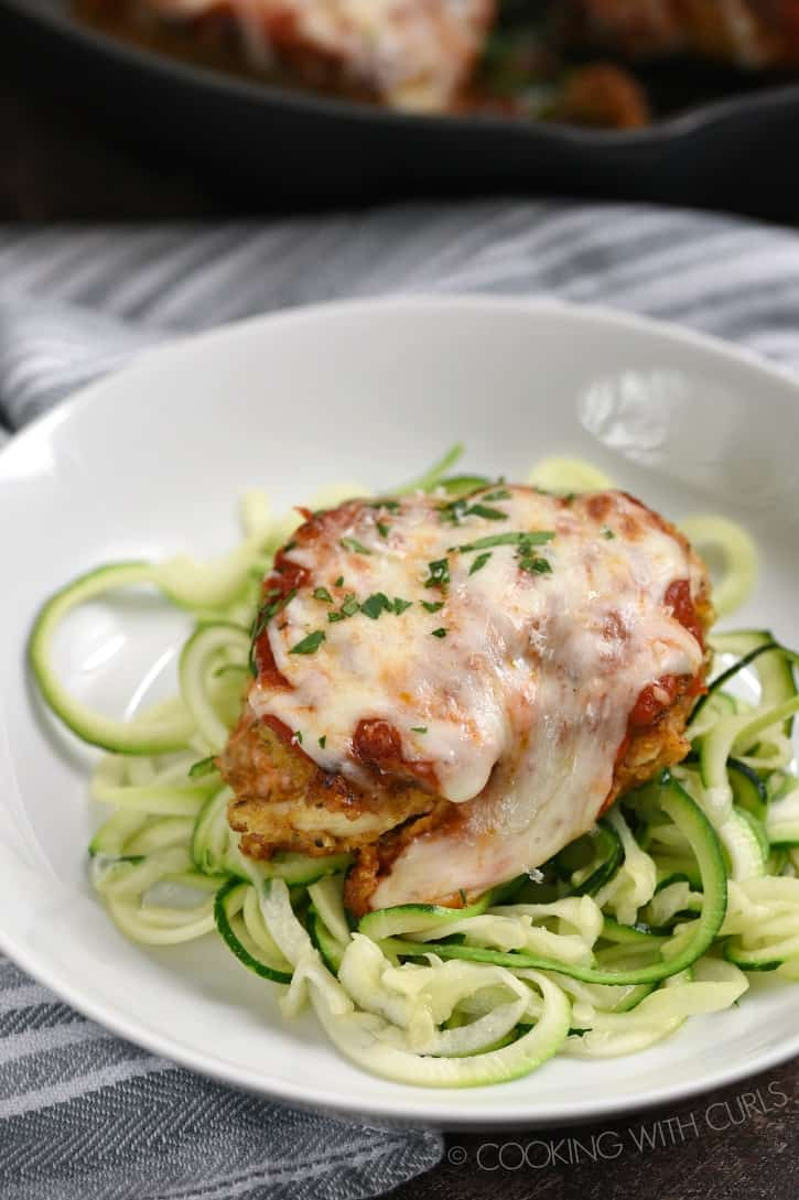 chicken parmesan with melted cheese on top sitting on a bed of zucchini noodles in a white pasta bowl